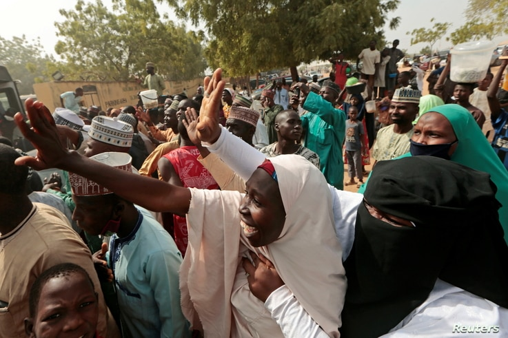People gather to receive schoolboys who were rescued by the Nigerian security forces in Katsina, Nigeria, December 18, 2020…