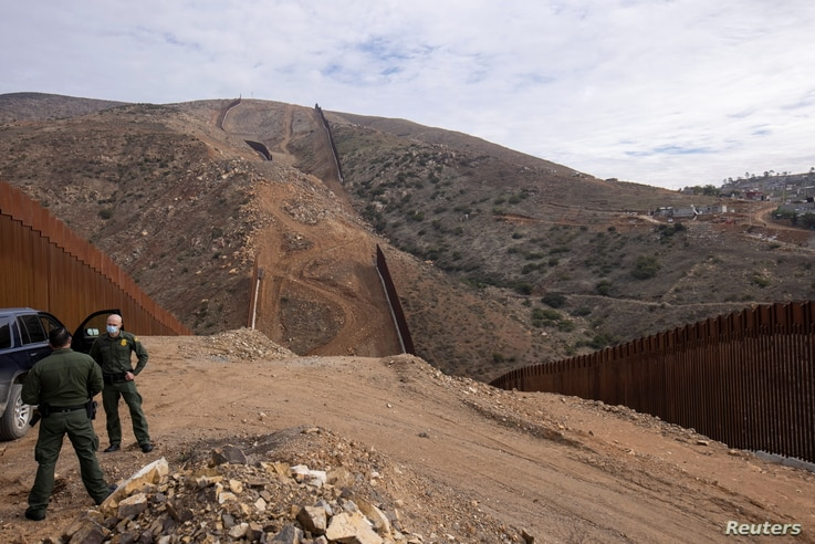 U.S. border patrol agents stand near the location of halted construction along the U.S. Border wall with Mexico as an…