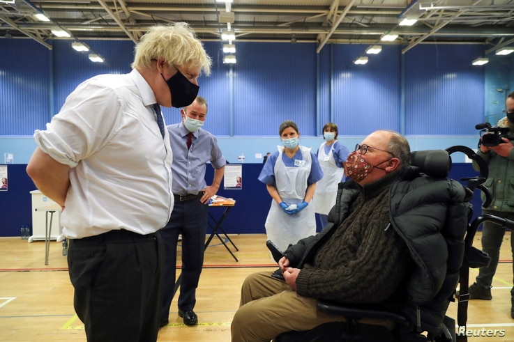 Britain's Prime Minister Boris Johnson speaks with a man waiting to receive an Oxford-AstraZeneca COVID-19 vaccine, during his…