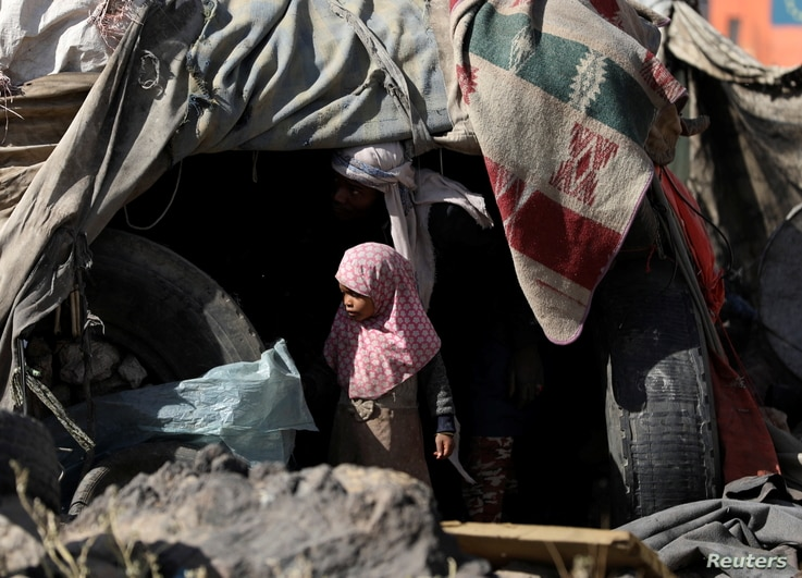 A girl stands outside her family's hut at a camp for internally displaced people on the outskirts of Sanaa, Yemen, March 1, 2021.