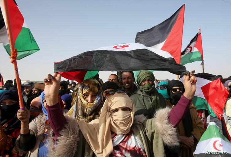 Sahrawi people carry flags as they gather to watch a parade at the Awserd refugee camp in Tindouf, Algeria February 27, 2021…