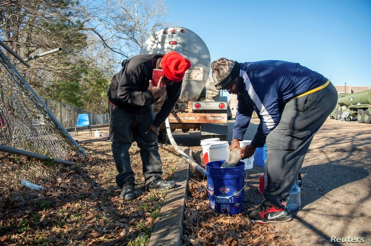 Ben Mitchell and Deon Sanders work at a public water distribution site after a recent bout of cold weather caused large numbers…