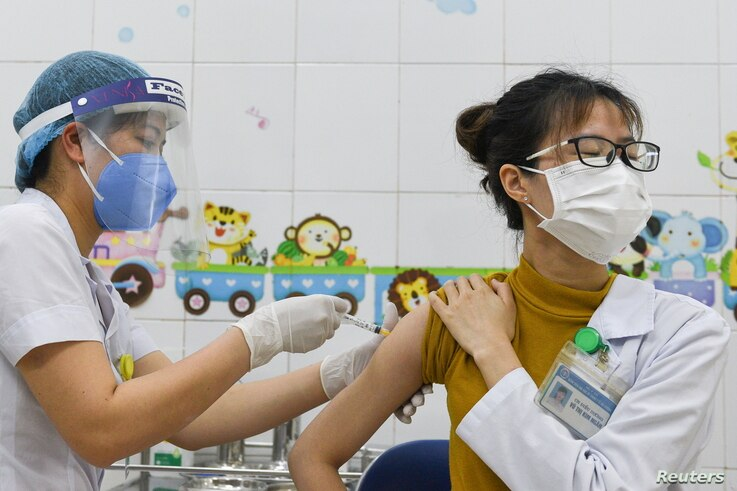 A woman receives a vaccine as Vietnam starts its official rollout of AstraZeneca's coronavirus disease (COVID-19) vaccine for...