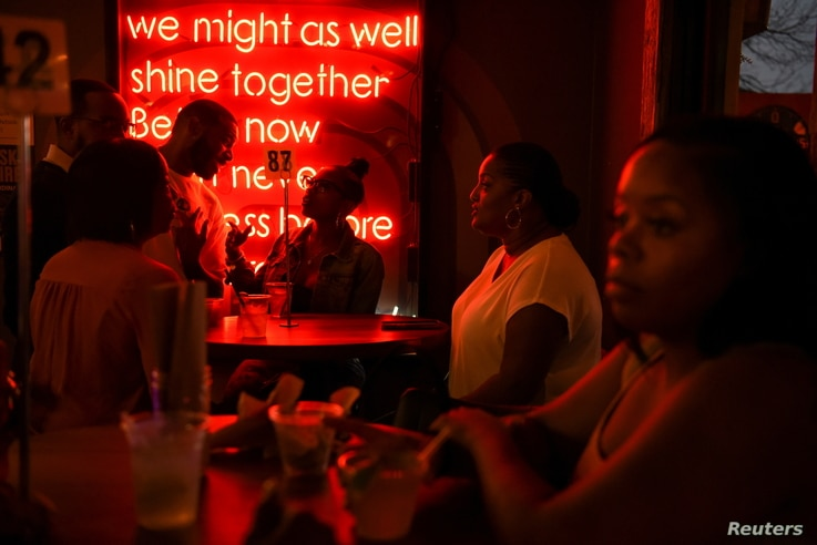 People share drinks and eat crawfish inside of Bar 5015 as the state of Texas lifts its mask mandate and allows businesses to...