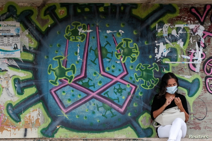A woman sits in front of a graffiti amidst the spread of the coronavirus disease (COVID-19) on a street in Brasilia, Brazil,...