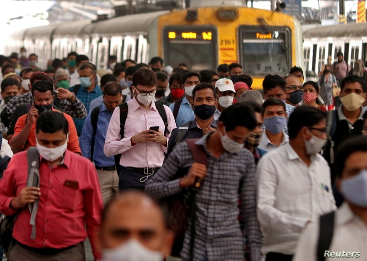 People wearing protective masks walk on a platform at the Chhatrapati Shivaji Terminus railway station, amidst the spread of…