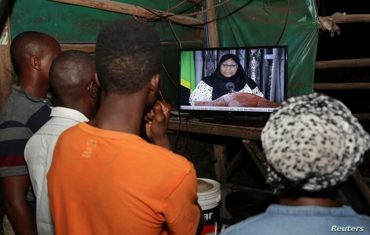 Residents watch the television announcement of the death of Tanzania's President John Magufuli, addressed by Vice President…