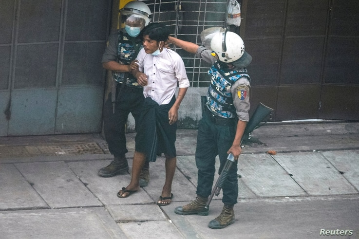 Riot police officers detain a demonstrator during a protest against the military coup in Yangon, Myanmar, March 19, 2021…