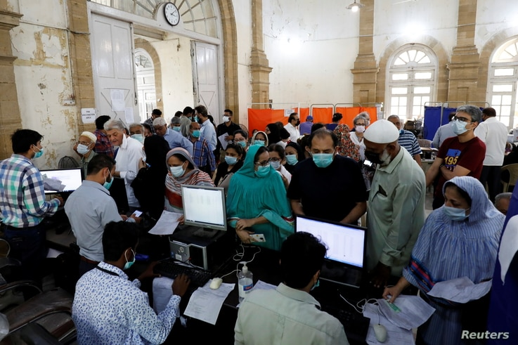 People gather for their coronavirus disease (COVID-19) vaccine doses, at a vaccination center in Karachi, Pakistan March 22,…