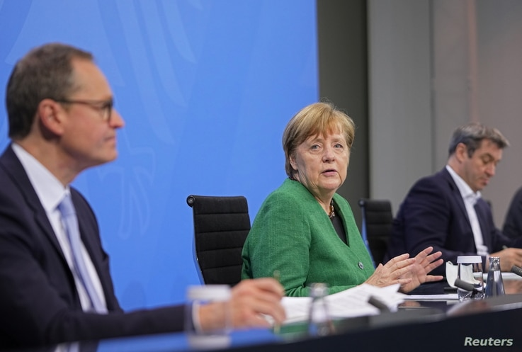 German Chancellor Angela Merkel attends a news conference after a meeting with state leaders to discuss options beyond the end…