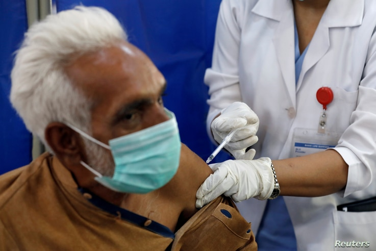 FILE PHOTO: An elderly resident receives the first dose of the coronavirus disease (COVID-19) vaccine, as the government…