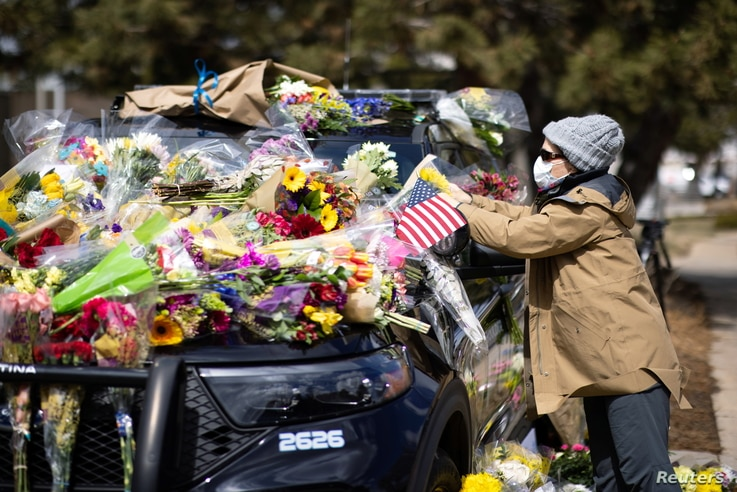 Joan Lutz, places a note that says, 'Thank you police officers, our hearts are grieving,' at a memorial for Officer Eric Talley...