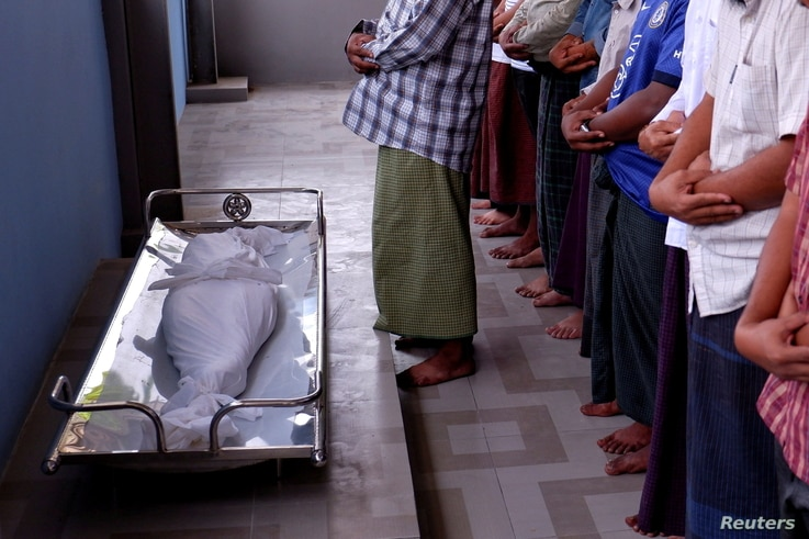 Muslim men pray during the funeral of 7 year-old girl Khin Myo Chit who was shot at her home during protests against military...