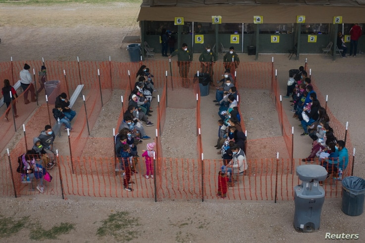 Asylum seeking migrant families from Central America await to be transported.