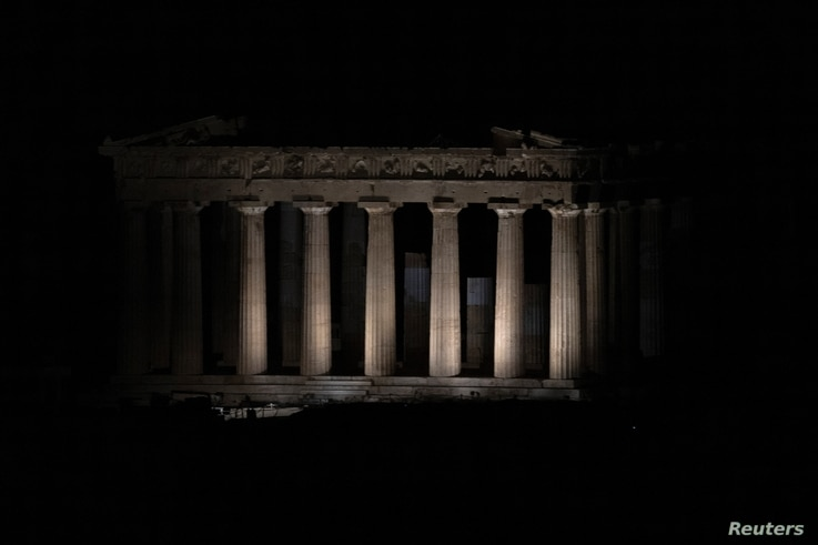 The ancient Parthenon is pictured just before the lights on the Acropolis hill shut down for Earth Hour in Athens, Greece March…