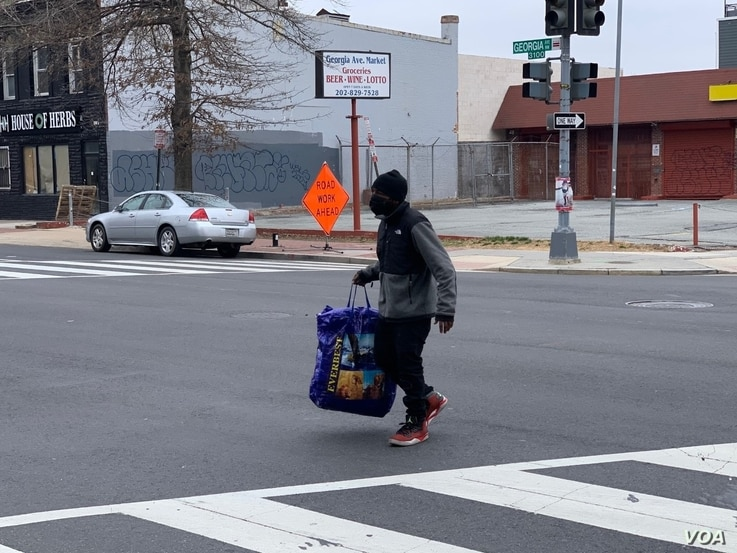 A man crosses the street in Washington's Park View neighborhood. (Chris Simkins/VOA)