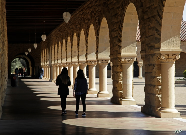FILE- In this March 14, 2019, file photo students walk on the Stanford University campus in Santa Clara, Calif. Even with a...