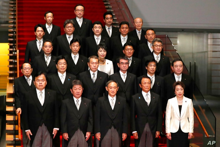 FILE - In this Sept. 16, 2020, file photo, Japan's Prime Minister Yoshihide Suga, front center, and his cabinet ministers pose...