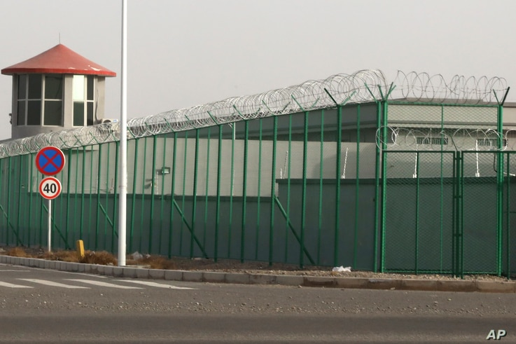 FILE - In this Monday, Dec. 3, 2018, file photo, a guard tower and barbed wire fence surround a detention facility in the…