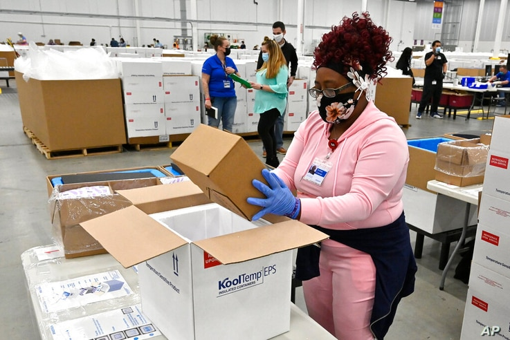An employee with the McKesson Corporation packs a box of the Johnson and Johnson COVID-19 vaccine into a cooler for shipping…