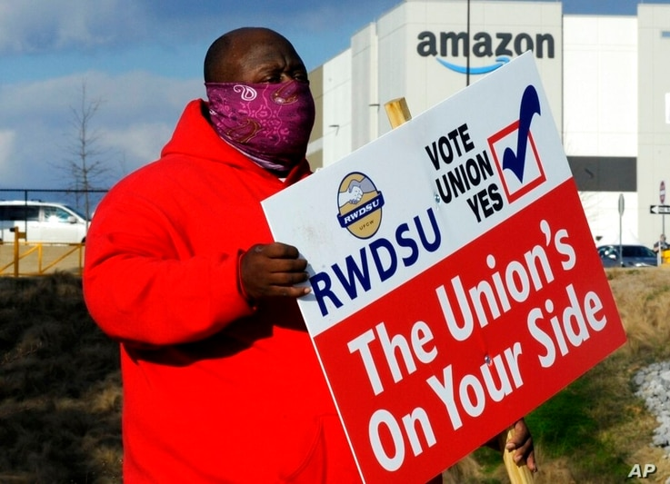 Michael Foster of the Retail, Wholesale and Department Store Union holds a sign outside an Amazon facility where labor is…