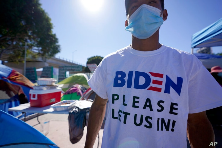 """A Honduran man seeking asylum in the United States wears a shirt that reads, """"Biden please let us in,"""" as he stands among tents…"""