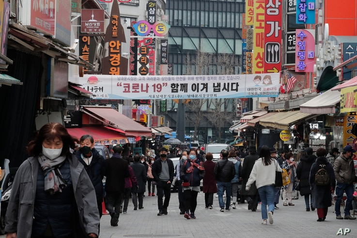 People wearing face masks walk through a market in Seoul, South Korea, Thursday, March 4, 2021. South Korea's central bank says…