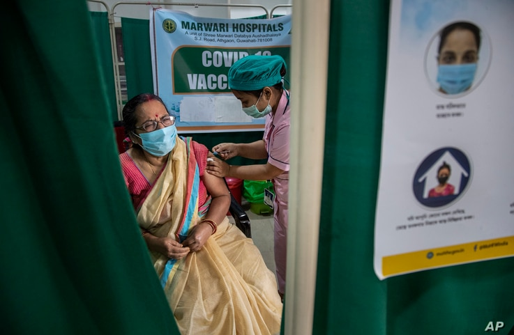 An elderly woman receives the COVID-19 vaccine at a private hospital in Gauhati, India, March 4, 2021.