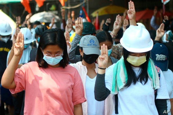 Anti-coup protesters flash the three-fingered symbol of resistance and bow in memory of those who died during recent security...