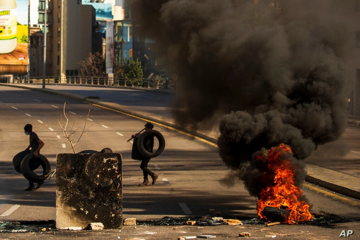 Protesters burn tires to close the main road, after the Lebanese pound hit a record low against the dollar on the black market,…