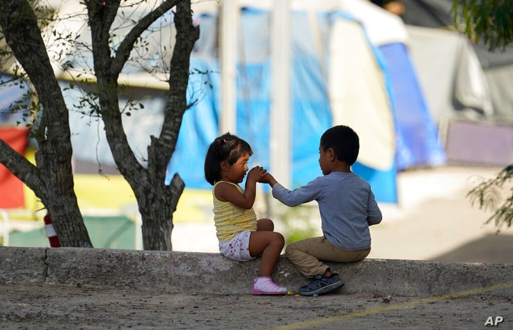 FILE - In this Nov. 18, 2020 file photo, children play at a camp of asylum seekers in Matamoros, Mexico. Some asylum seekers...