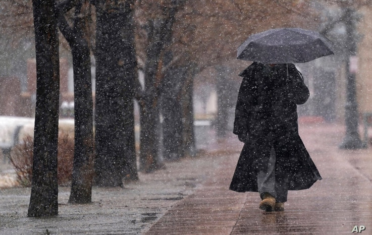 A pedestrian uses an umbrella for cover as a storm sweeps over the intermountain West, March 13, 2021, in…