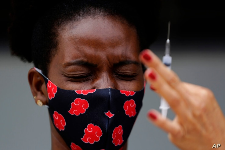 A woman reacts to seeing a syringe of the Sinovac vaccine for COVID-19 as health workers vaccinate residents in the Kalunga Vao…