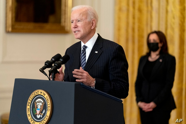 President Joe Biden, accompanied by Vice President Kamala Harris, right, speaks about COVID-19 vaccinations in the East Room of…