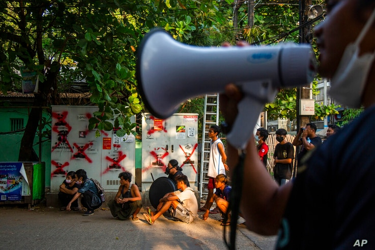 Anti-coup protesters and residents monitor police and military occupying a roadblock in Yangon, Myanmar, Friday, March 19, 2021…