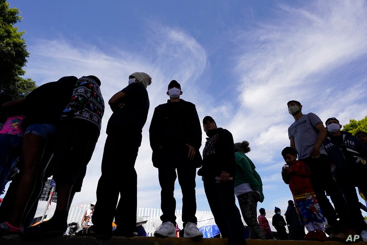 Migrants line up for a free meal at a makeshift camp of migrants at the border port of entry leading to the United States,…