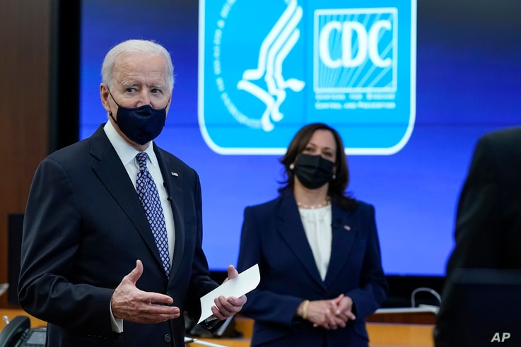 President Joe Biden speaks as Vice President Kamala Harris listens during a COVID-19 briefing at the headquarters for the…