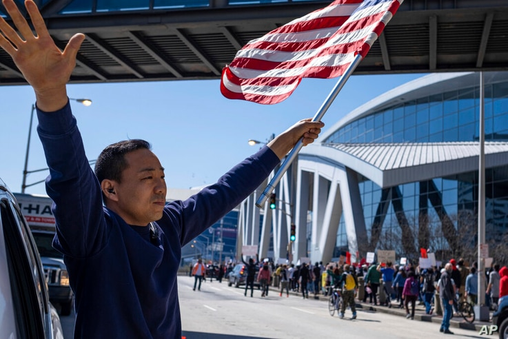 """Hailun Song waves a U.S. flag and cheers marchers as a """"stop Asian hate"""" rally in downtown Atlanta passes by Saturday afternoon…"""