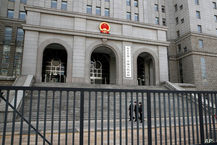 Policemen wearing face masks patrol at the compound of No. 2 Intermediate People's Court in Beijing, Monday, March 22, 2021. The...