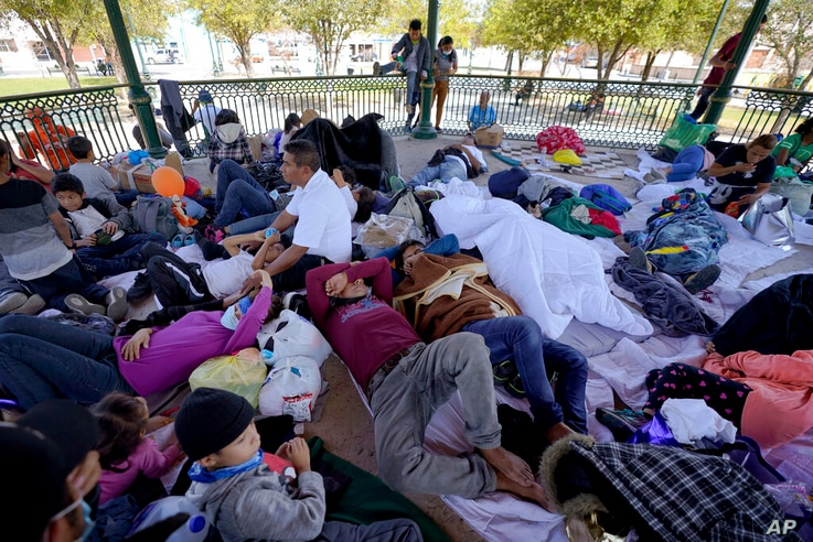A group of migrants rest on a gazebo at a park after they were expelled from the U.S. and pushed by Mexican authorities off an…
