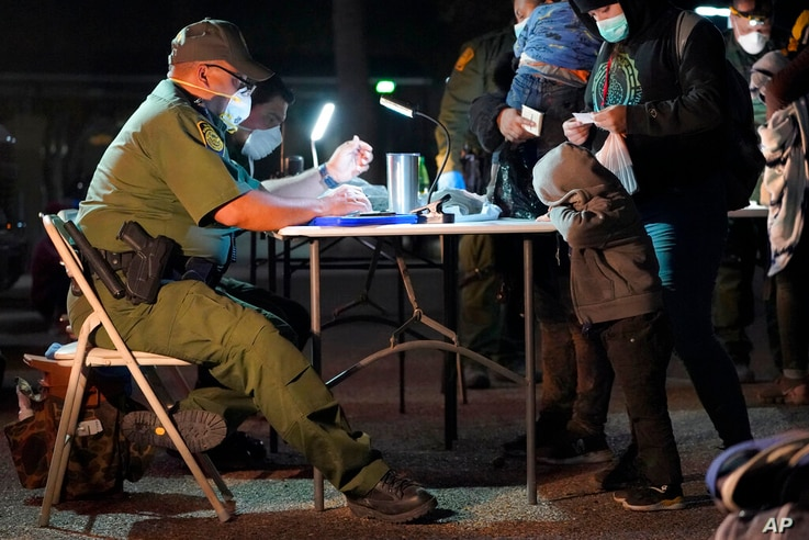 A child rests its head on a table as a U.S. Customs and Border Protection officer processes migrants after they crossed into…