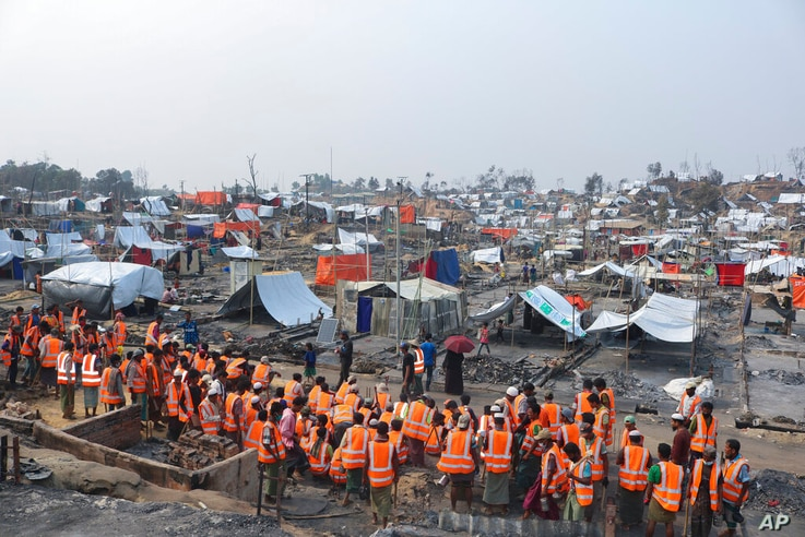 Volunteers from aid agencies who arrived to rebuild shelters for Rohingya refugees who lost their dwellings to a devastating…