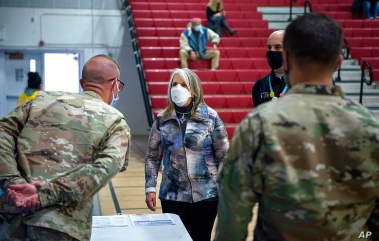 New Mexico Governor Michelle Lujan Grisham talks with National Guardsmen after receiving her Pfizer COVID-19 vaccine during a…