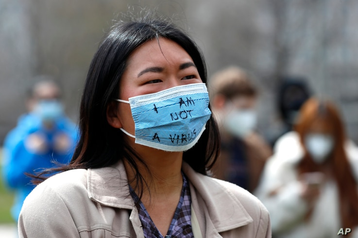 """A demonstrator wearing a mask saying """"I am not a virus"""" listens to a speech at a rally against Asian hate crimes, Saturday,…"""