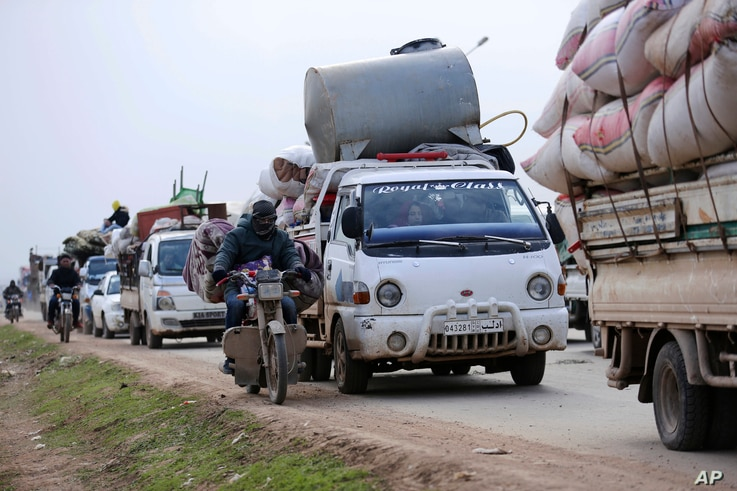 FILE - In this Jan. 29, 2020 file photo, Syrians flee the advance of government forces towards the Turkish border, in Idlib…