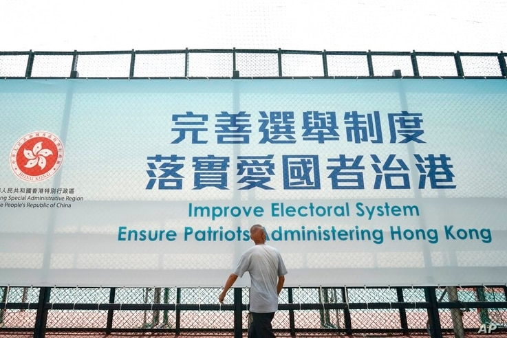 A man walks past a government advertisement to promote the new Hong Kong electoral system reform, in Hong Kong, March 30, 2021…