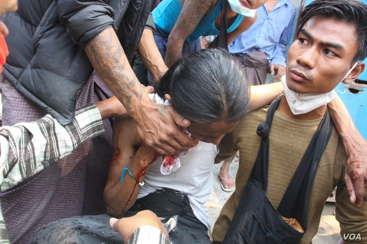 Protesters attend to a person wounded during demonstrations in Mandalay, a city in Myanmar, March 3, 2021. (Htet Aung Khant/VOA Burmese)