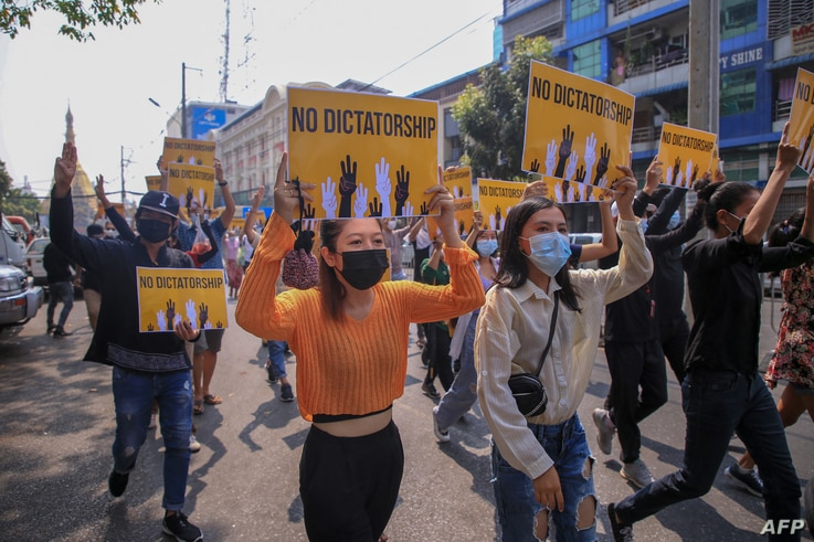 This photo received from an anonymous source via Facebook March 26, 2021, shows protesters carrying signs during a demonstration against the military coup in Yangon, Myanmar.