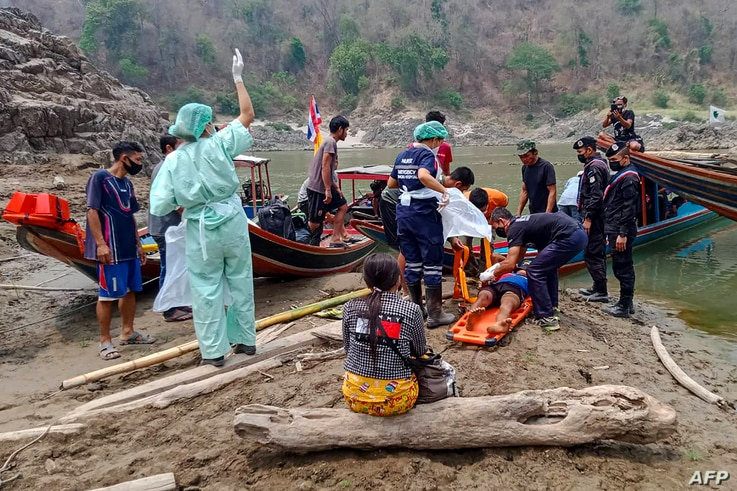 An injured Myanmar refugee is transported to a hospital in Mae Sam Lap, Thailand, after crossing the Salween river from the Myanmar side while while fleeing from airstrikes in Myanmar's eastern Karen state following the February military coup.