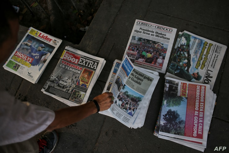 FILE - A Venezuelans picks a newspaper in Caracas, May 1, 2019, after a day of violent clashes on the streets of the capital spurred by opposition leader Juan Guaido's call on the military to rise up against President Nicolas Maduro.